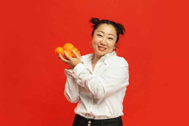 休日の味。ハッピーチャイニーズニューイヤー2020。伝統的な服で赤い背景にみかんを保持しているアジアの若い女性。 無料写真