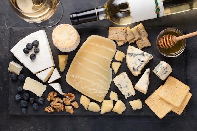 Tasting cheese dish on a dark stone plate. Premium Photo