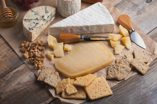 Tasting cheese dish on a wooden background. Premium Photo