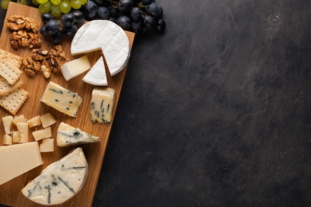 Tasting cheese dish on a wooden plate. Premium Photo