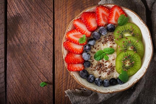 Вкусная и полезная овсяная каша с фруктами, ягодами и семенами льна. здоровый завтрак. фитнес-питание. правильное питание. квартира лежала. вид сверху Бесплатные Фотографии