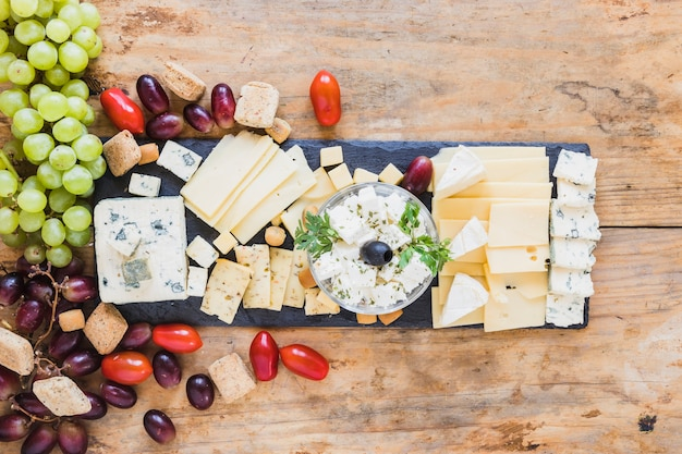 Tasty appetizers with cheese plate, tomatoes and grapes Free Photo