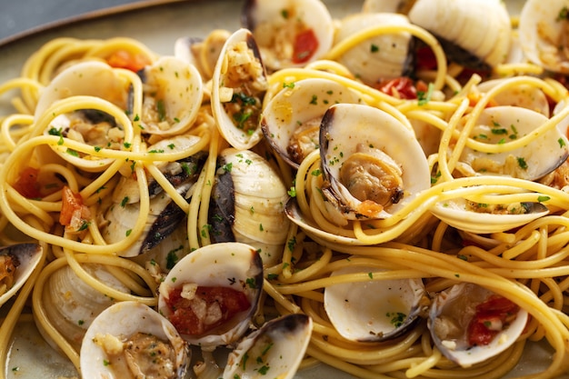Tasty appetizing fresh homemade clams alle vongole seafood pasta with garlic and white wine on plate. closeup. Free Photo