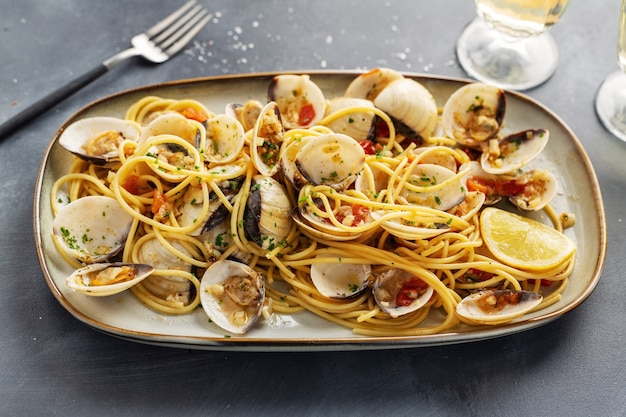 Tasty appetizing fresh homemade clams alle vongole seafood pasta with garlic and white wine on plate. closeup. Premium Photo
