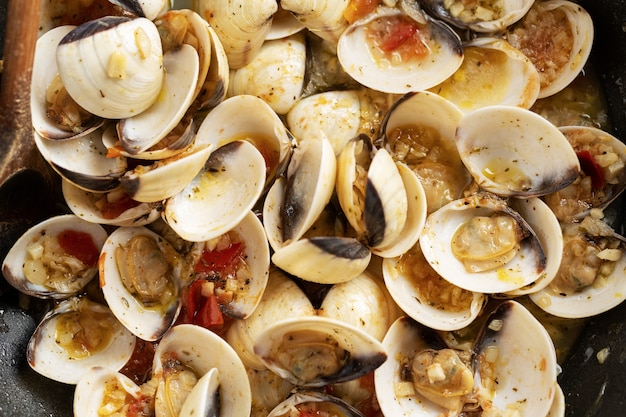 Tasty appetizing fresh homemade clams alle vongole with garlic and white wine on pan. closeup. Free Photo