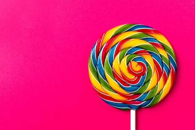Tasty appetizing party accessory sweet swirl candy lollypop on pink background top view Free Photo
