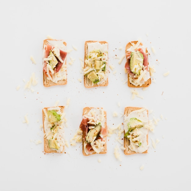 Tasty arranged toasts with cheese; avocado and bacon on white background Free Photo