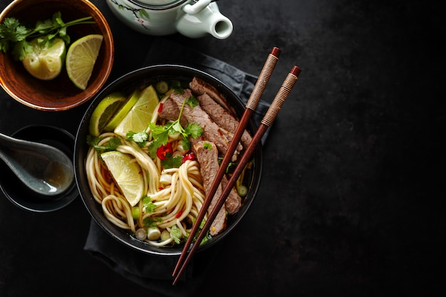 Tasty asian classic soup with noodles and meat Premium Photo