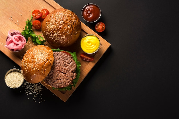 Tasty beef burgers on a wooden board with sauces Free Photo