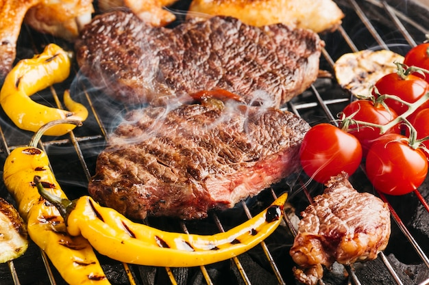 Tasty beef steaks on the grill with yellow chili and cherry tomato Free Photo