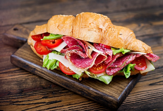 Tasty breakfast. appetizing croissant with salami and, cheese and tomatoes Free Photo