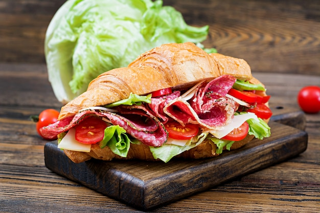 Tasty breakfast. appetizing croissant with salami and, cheese and tomatoes Premium Photo