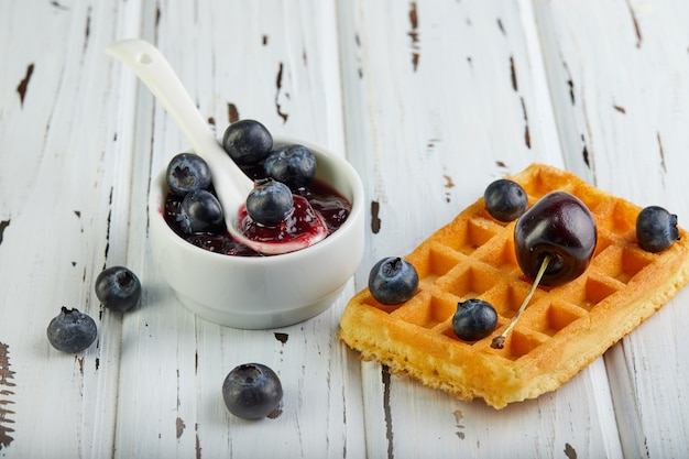 Tasty breakfast. belgian waffles with whipped cream blueberries and jam on a wooden white Premium Photo