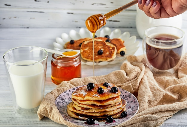 Tasty breakfast. a stack of pancakes with honey syrup a glass of milk, espresso coffee and honey on a wooden white Premium Photo
