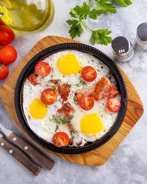 Вкусный завтрак с яичницей, беконом и овощами на сковороде Premium Фотографии