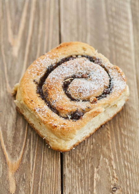 Tasty buns with raisins on a brown rustic wooden table. fresh bakery. breakfast. bread. top view Premium Photo