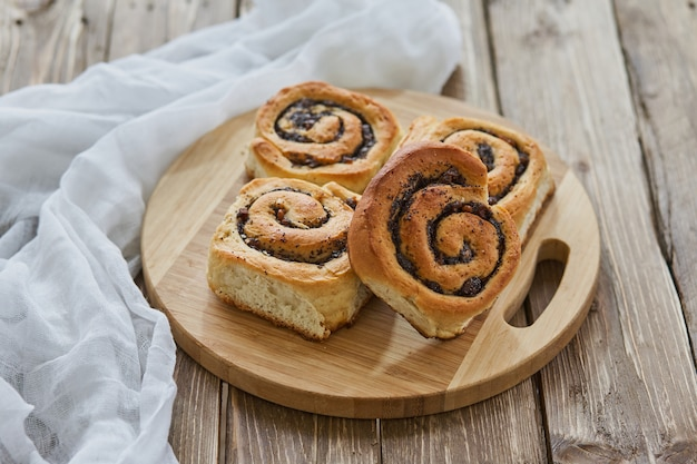 Вкусные булочки с изюмом на коричневый деревенский деревянный столик. Premium Фотографии