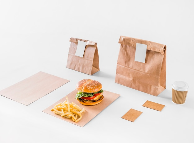 Tasty burger; french fries; parcels and disposal cup on white surface Free Photo