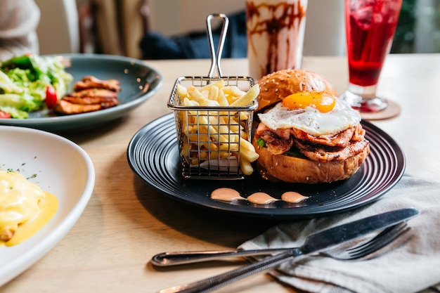 Tasty Burger With Fried Egg Served With Fries In Black Plate On