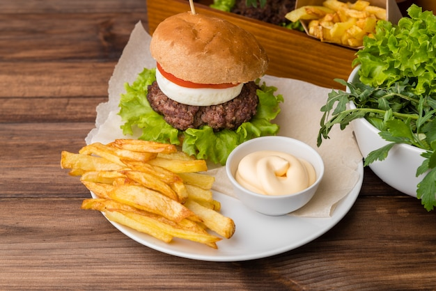 Tasty burger with sauce and french fries Free Photo