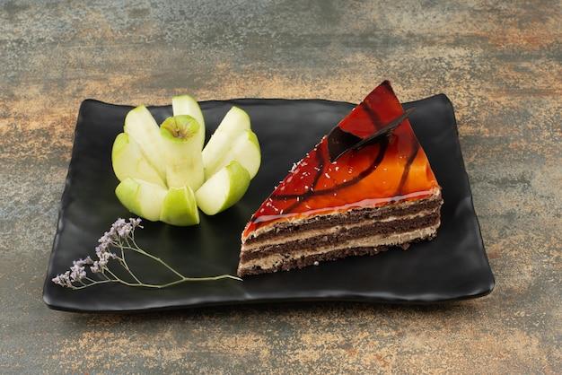 Вкусный торт на тарелке с нарезанным зеленым яблоком на мраморной поверхности. Бесплатные Фотографии