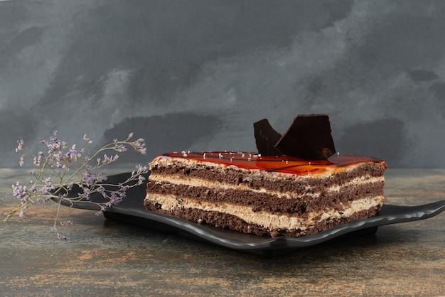 大理石の表面に花が付いたプレート上のおいしいケーキ。 無料写真