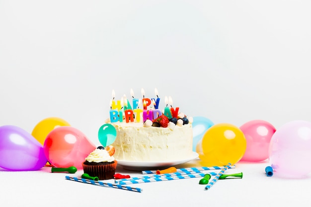Tasty cake with berries and happy birthday title near colourful balloons Free Photo