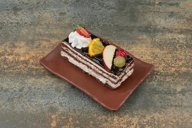 大理石の背景のプレートにフルーツとおいしいケーキ。高品質の写真 無料写真