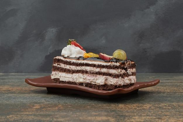 Вкусный торт с фруктами на тарелке на мраморном столе. Бесплатные Фотографии