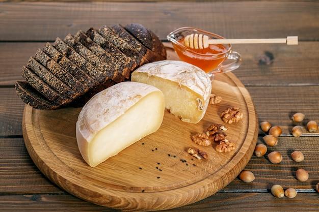 Вкусный сыр, мед, хлеб и орехи. концепция здорового питания Premium Фотографии