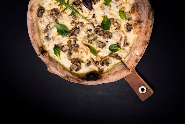 Tasty cheesy mushroom pizza and basil leaves on wooden board over black backdrop Free Photo