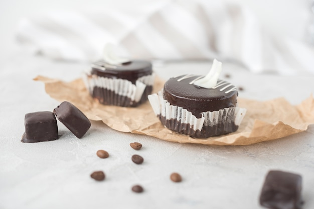 Tasty chocolate cupcake and coffee beans on parchment paper Free Photo