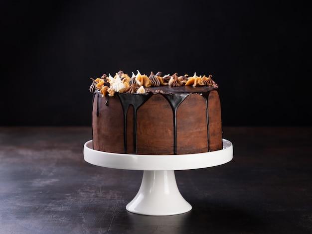 Tasty chocolate drip cake with melting chocolate on dark Premium Photo