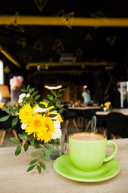 Tasty coffee near beautiful flower vase on wooden table Free Photo
