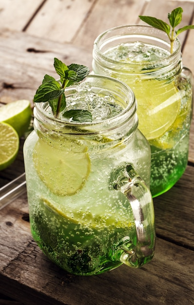 Tasty cold fresh drink lemonade with lemon, mint, ice and lime in glass on wooden table. Closeup. Free Photo