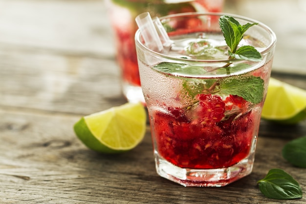 Tasty cold fresh drink lemonade with raspberry, mint, ice and lime in glass on wooden background. closeup. Free Photo