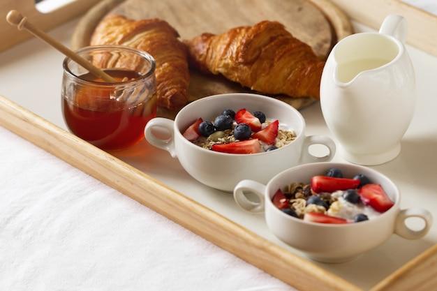Вкусный красочный завтрак с овсянкой, йогурт, клубника, черника, мед и молоко на белом фоне. завтрак в постель. копирование пространства. вид сверху. Бесплатные Фотографии