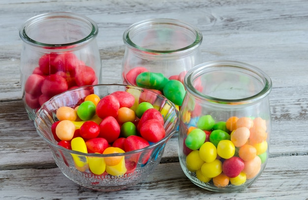 Tasty colorful candies in glass bowl and jars Premium Photo