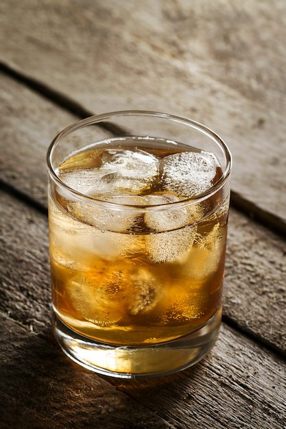 Tasty colorful cold alcohol drink whiskey with ice in glass on wooden table. Free Photo