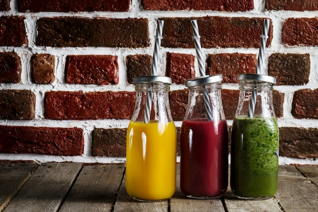 Tasty colorful fresh homemade smoothies in glass jars on wooden table. kitchen background. Free Photo