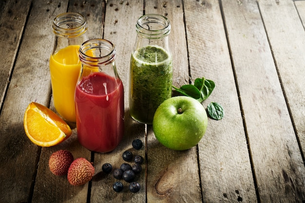 Tasty colorful fresh homemade smoothies in glass jars on wooden table. Healthy, detox concept. Free Photo