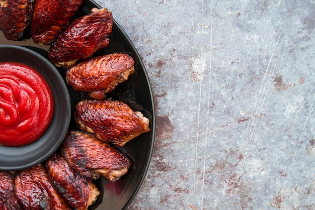 Tasty crispy chicken wings with sauce in bowl over concrete floor Free Photo