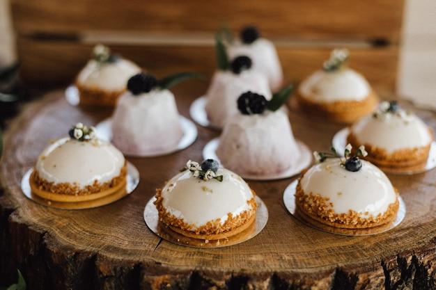 Вкусные украшенные сливочные десерты на деревянном подносе Бесплатные Фотографии