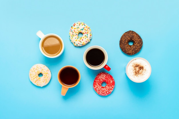 Tasty donuts and cups with hot drinks on a blue surface. concept of sweets, bakery, pastries, coffee shop, friends, friendly team. flat lay, top view Premium Photo