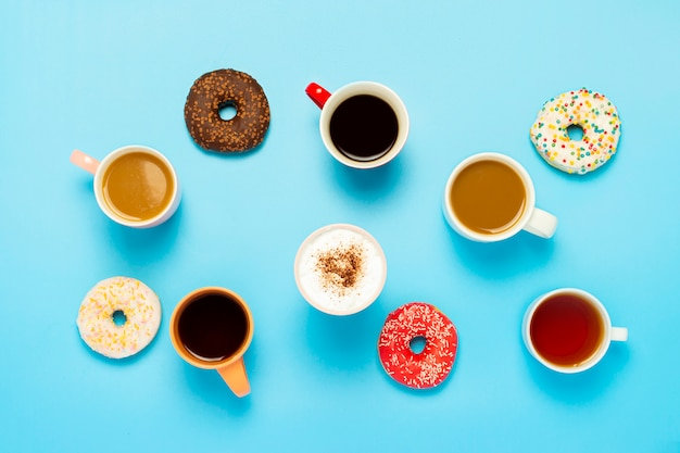 Tasty donuts and cups with hot drinks, coffee, cappuccino, tea on a blue surface. concept of sweets, bakery, pastries, coffee shop, meeting, friends, friendly team. flat lay, top view Premium Photo
