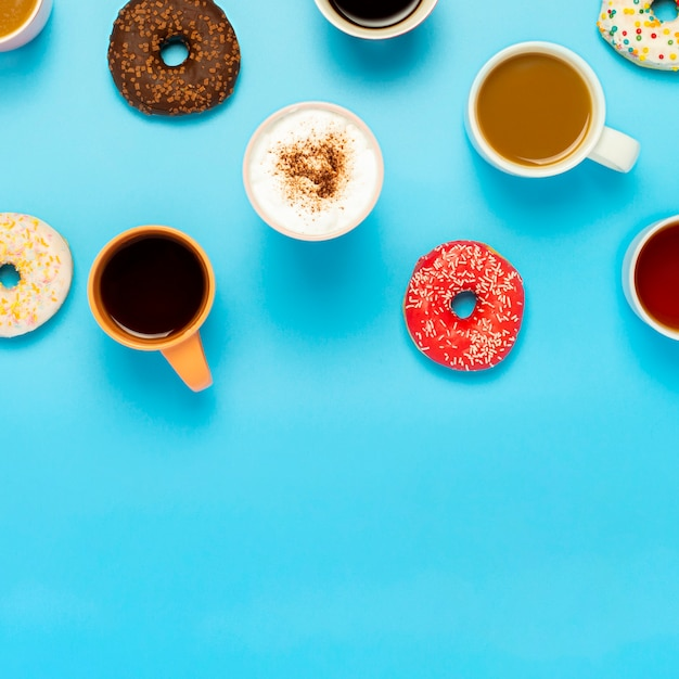 Tasty donuts and cups with hot drinks, coffee, cappuccino, tea on a blue surface. concept of sweets, bakery, pastries, coffee shop, meeting, friends, friendly team. square. flat lay, top view Premium Photo