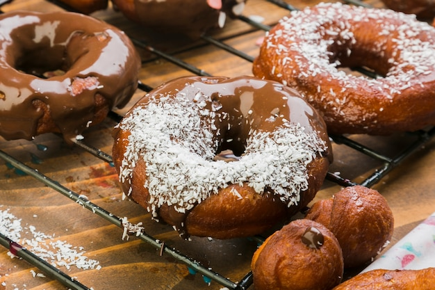 Tasty donuts with chocolate syrup and grated coconut on baking tray Free Photo