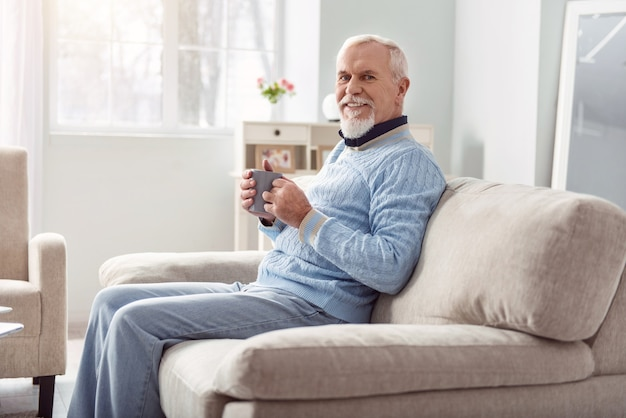 Tasty drink. upbeat senior man sitting on the sofa in the living room and smiling while drinking coffee Premium Photo