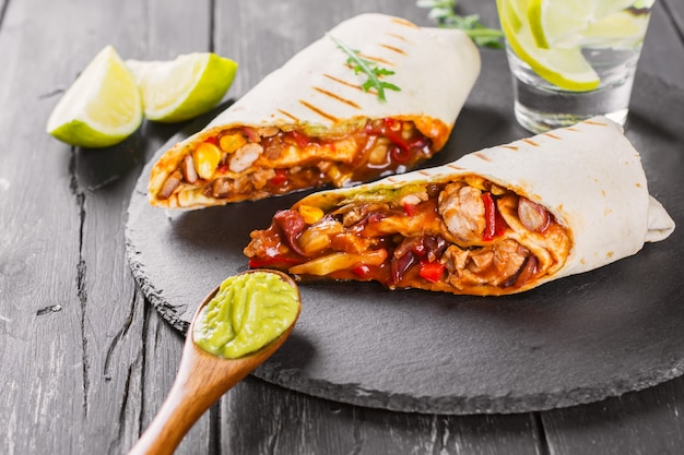 Tasty fast food: mexican burritos with guacamole sauce on black wooden background Premium Photo