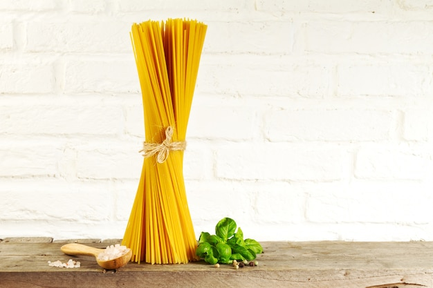 Tasty fresh colorful italian food raw spaghetti on kitchen table on kitchen background. cooking or healthy food concept. Free Photo